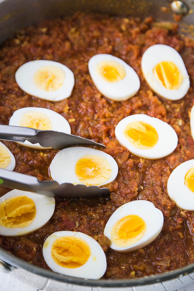 Hard cooked eggs that have been added to the skillet of curry sauce, cut-side up.