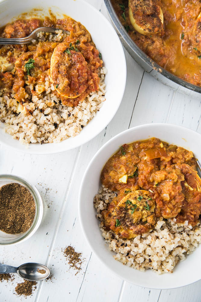 Egg curry served in two bowls with roasted cauliflower rice and sprinkle of garam masala.