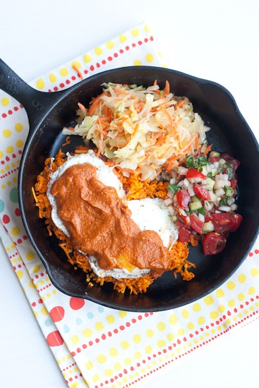 Paleo Huevos Rancheros Skillet - Sweet potato hash browns, drippy fried eggs, tangy cabbage slaw, and fresh cucumber pico de gallo. All topped with a slathering of enchilada sauce. It really doesn't get better than this.