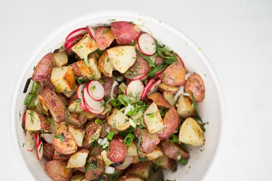 This is a fresh, mayo-free take on a potato salad. Tender roasted potatoes are tossed with a herby, mustardy vinaigrette. You'll never go back to regular potato salads. | perrysplate.com