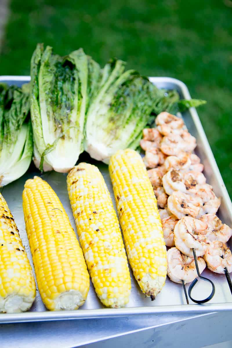 This is a fun, Southwest twist on a Caesar Salad with grilled romaine. (Yes, you can grill lettuce! It works!) The Cilantro-Lime Caesar Dressing is my favorite part. | perrysplate.com #caesarsalad #grilledshrimp #grilledcorn