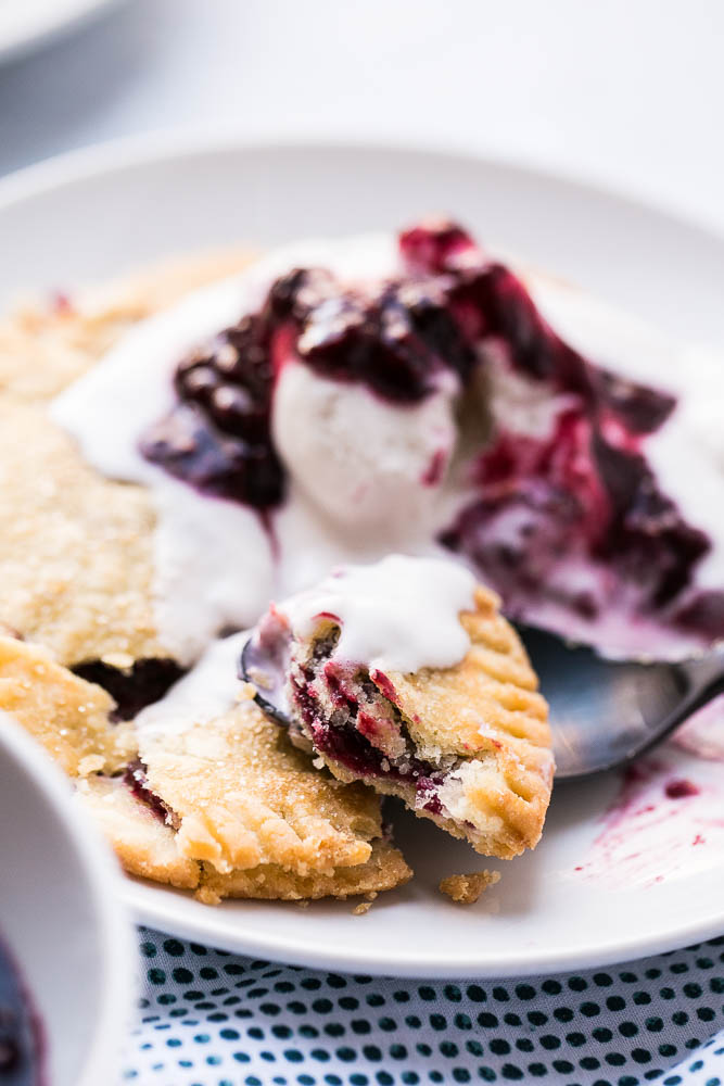 Gluten-Free Berry Hand Pies are made with the best gluten-free pie crust and easy filling! Top them with ice cream and extra berry sauce! | perrysplate.com