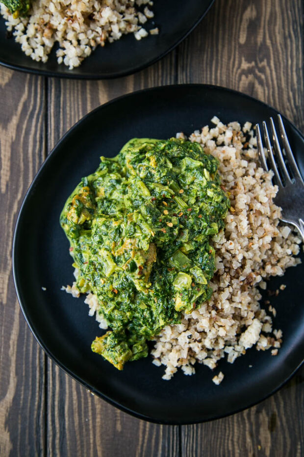Chicken Saag over roasted cauliflower rice on a black plate.