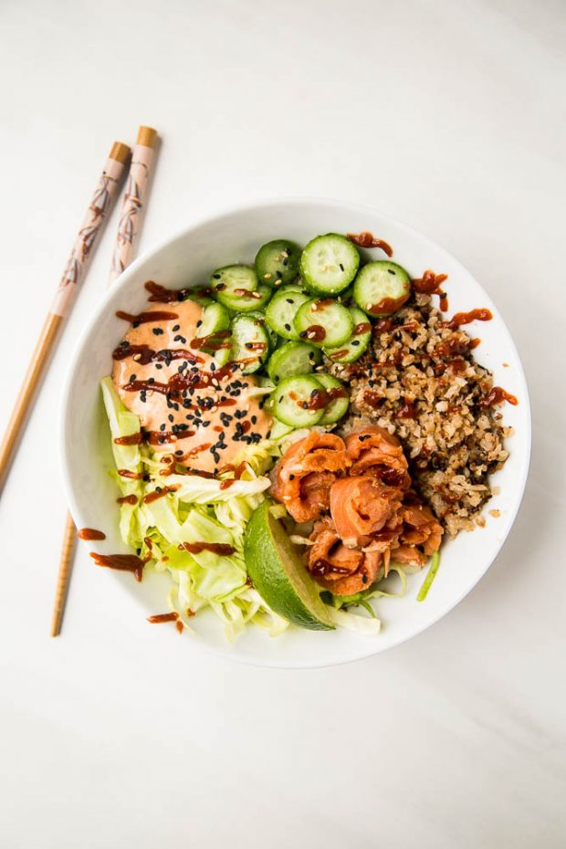 A finished sushi-style bowl using the sriracha lime gravlax, sriracha mayo, roasted cauliflower rice, shredded cabbage, and sliced cucumber.