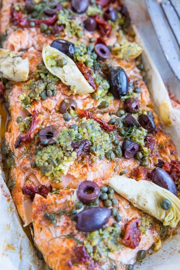 Salmon in parchment covered with Mediterranean-inspired toppings like basil pesto, artichoke hearts, kalamata olives, capers, and sun-dried tomatoes.
