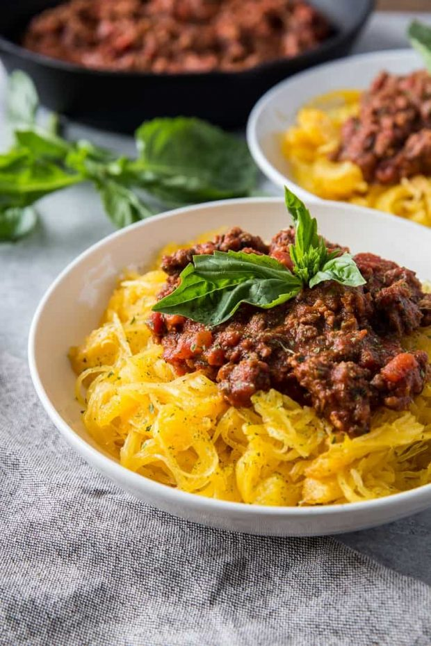 White bowls of spaghetti squash covered in a hearty bolognese sauce and topped with fresh basil.
