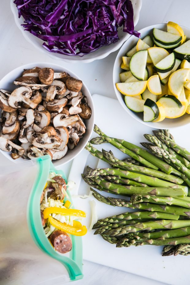 Prepped bowls of shredded cabbage, sliced mushrooms, sliced summer squash, chopped asparagus