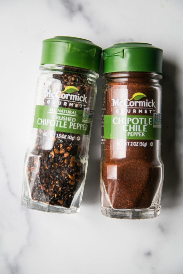 Small spice jars of chipotle chile powder and crushed chipotle peppers.