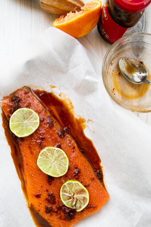 Sweet Chipotle Salmon prepped on a piece of parchment with lime slices on top.