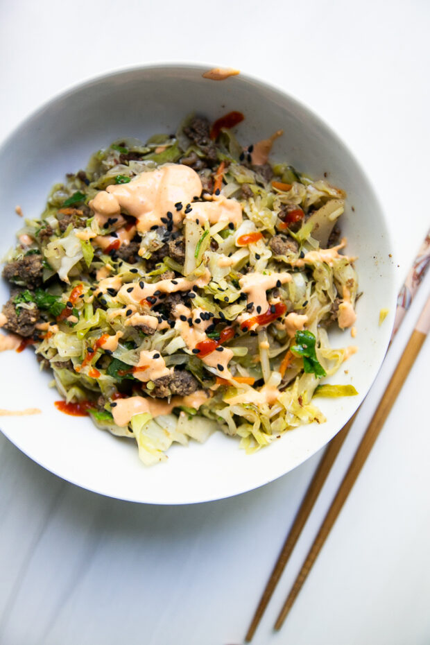 Egg Roll in a Bowl with ground beef topped with sriracha mayo and black sesame seeds. Easy paleo recipe.