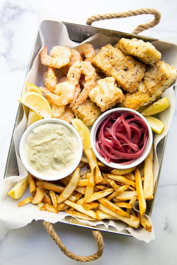 This Aruba-inspired fish fry is one of our favorite meals and memories from a fun family trip. Image shows a tray with fried pieces cod & shrimp, french fries, garlic aioli, and pickled red onions.