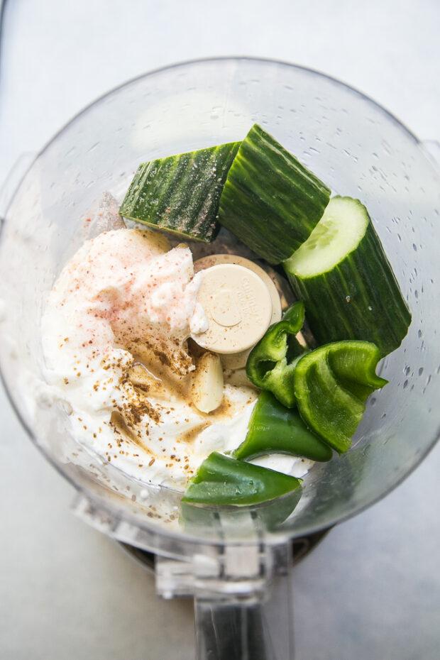 Ingredients for Cucumber Yogurt Dressing in a food processor -- Greek Yogurt, English cucumber, jalapeno, salt, cumin, lemon juice.