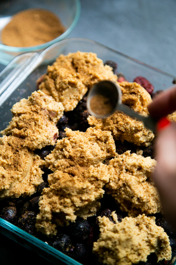 A sprinkle of cinnamon, coconut sugar, and cloves create a cracked snickerdoodle-like topping for the berry cobbler.
